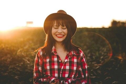 夕日を背に草むらの中に立ちキュートな笑顔を見せる女の子
