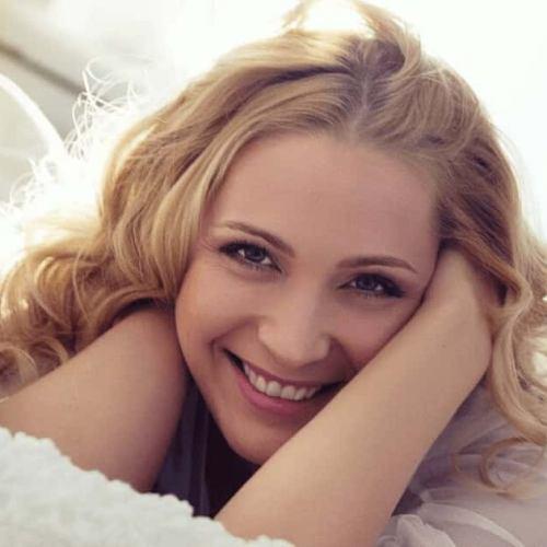 まっ白なシーツを身にまといベッドの上で微笑むブロンドヘアの既婚者女性