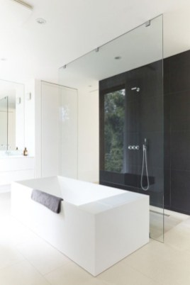 Nice and minimalist bathroom with the glass wall with a concrete 17