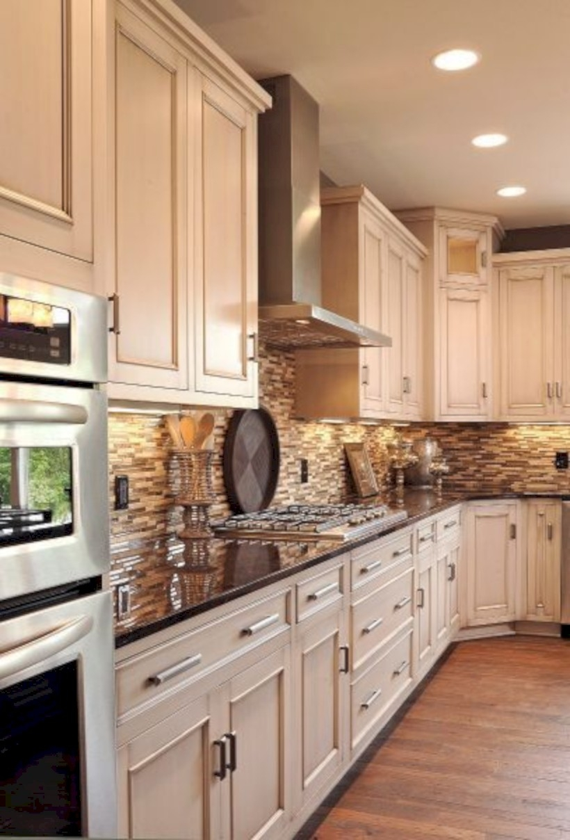 Beautiful creamy white kitchen cabinets with stone tile backsplash