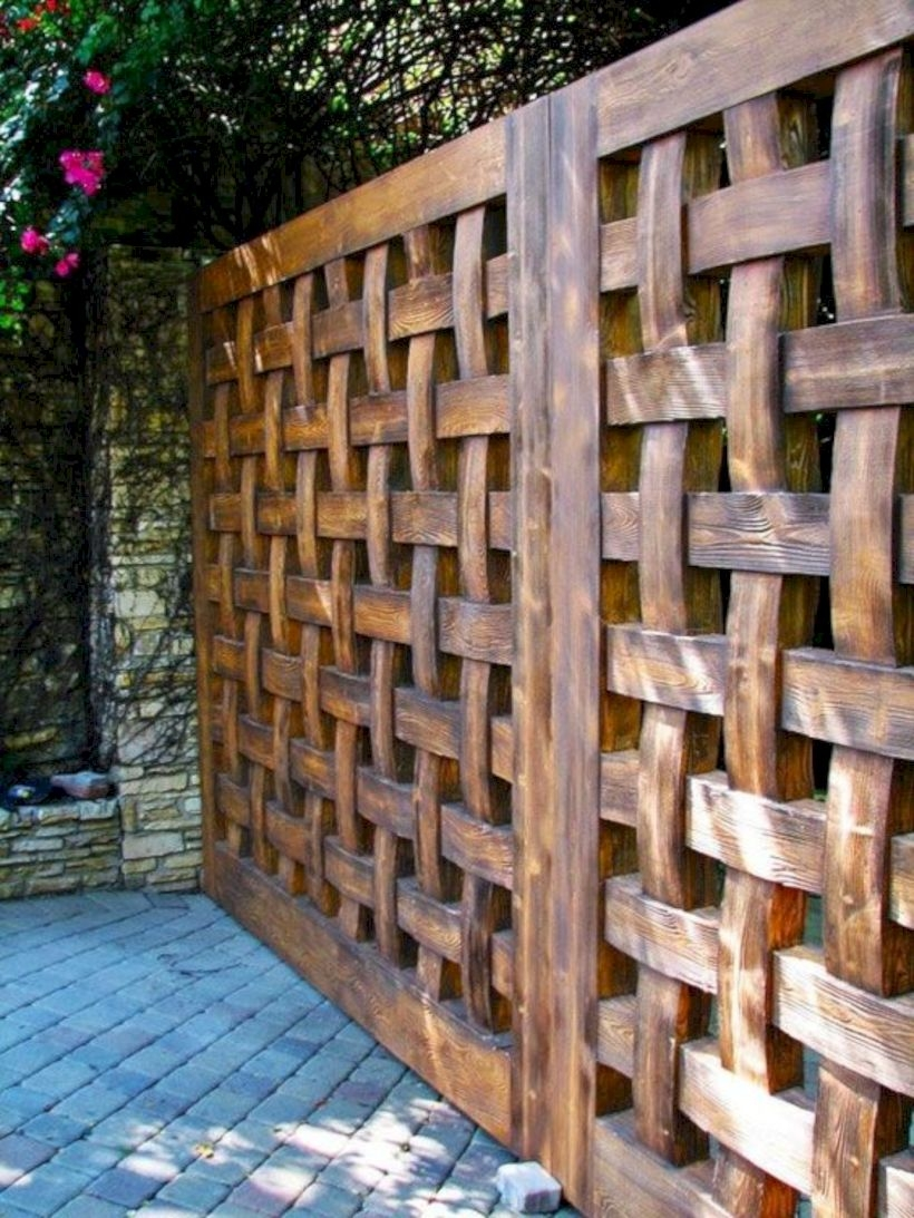 A solid wooden fence in a lattice style