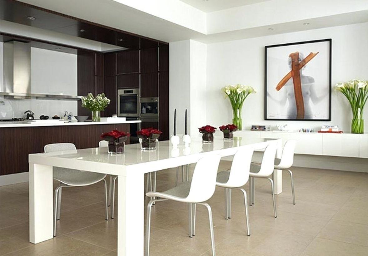 An amazing modern white dining room with white walls, white rectangular tables, white chairs, and white flowers to create room more beautiful