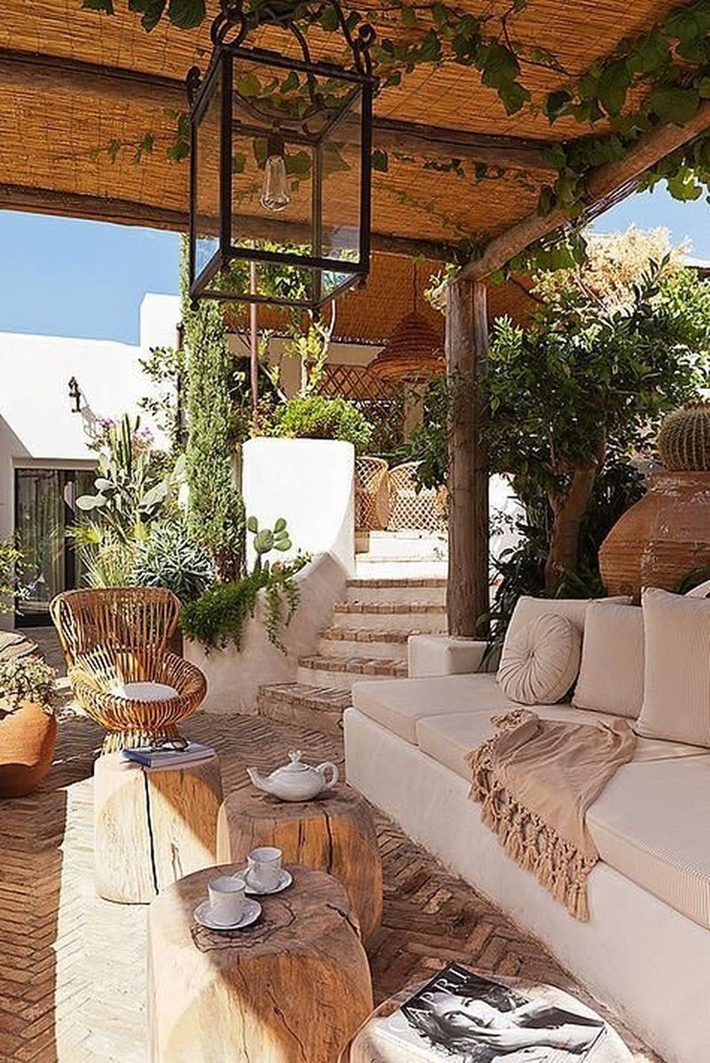 An awesome boho exterior with a hanging lamp, vines on the ceiling, beams table, a rattan chair, light grey sofa to decorate your home exterior design