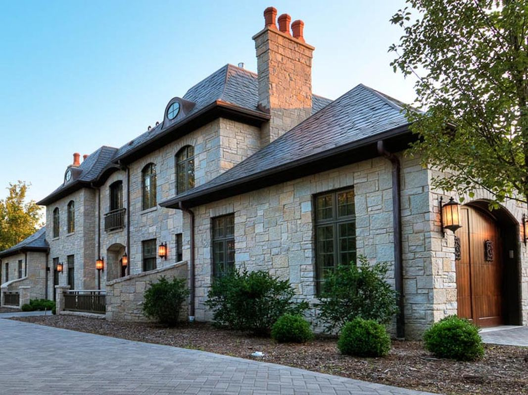 Classic exterior design with light grey stone walls, classic window, chimney and old wooden door to perfect your classic home
