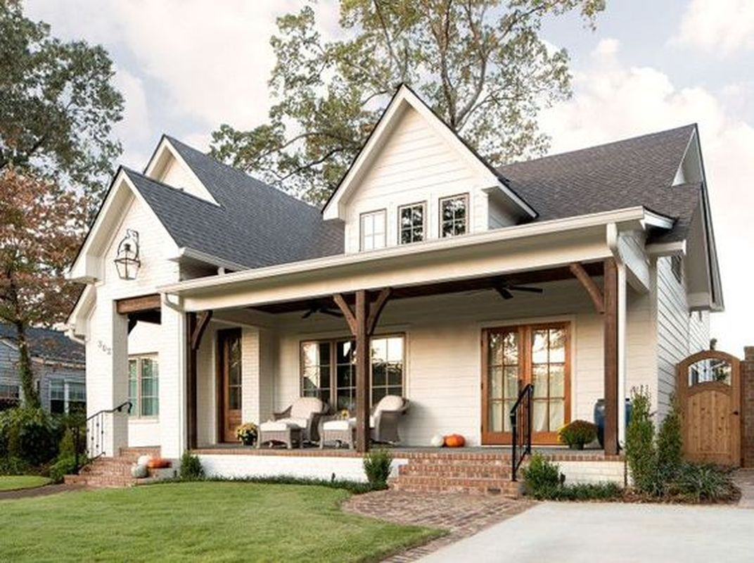 Simple farmhouse design elements in this exterior are dark roof, white siding, white trim, wood beam porch and doors