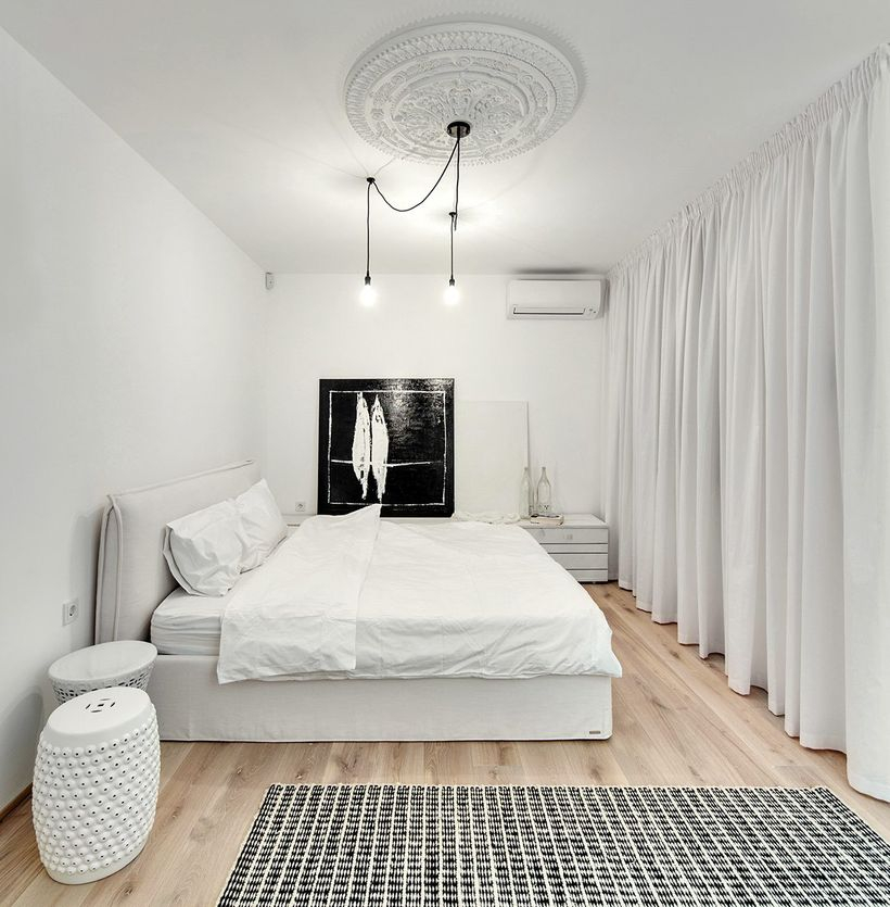 Simple white bedrooms with white beds, white blankets, large white curtains, white round chairs, wooden floors to make it more comfortable