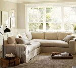 A beautiful small living room design with white and light gray walls, a light gray leeter l sofa, big windows, a rattan basket, and floor lamp