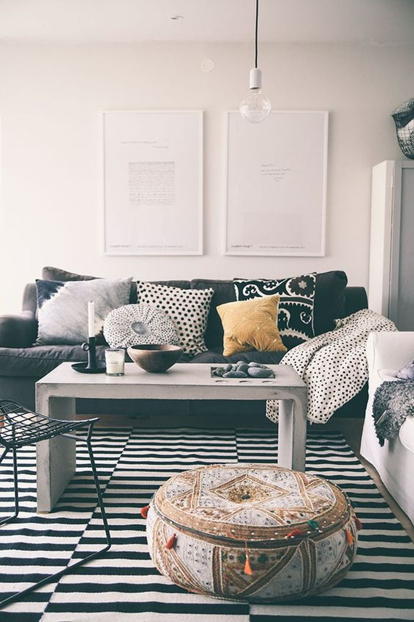 A gorgeous black and white living room design with white walls, a striped patterned carpet, black and white sofas