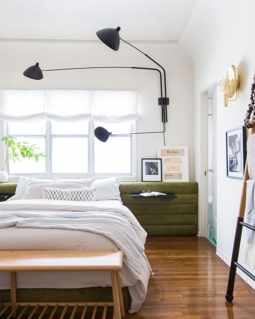A modern farmhouse bedroom design with a wooden night stand on beside, wooden vinyl floor, big windows, and decorative lighting to create perfect lighting
