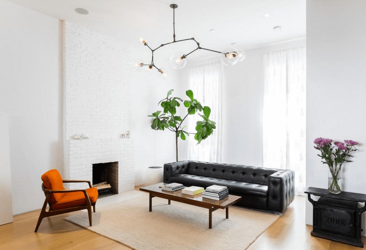 A modern farmhouse living room design with white walls, a white fireplace, white overlay curtains, a wooden coffee table, decorative lighting, house plants to create fresh room