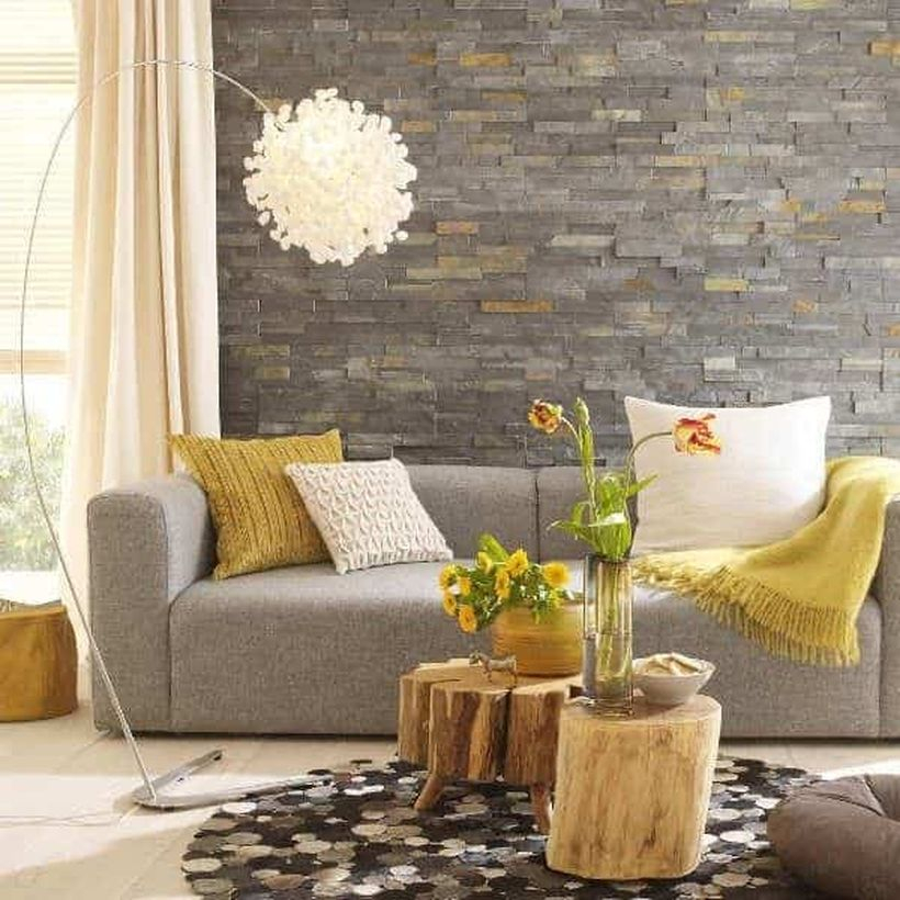 A modern living room design with natural stone brick walls, a window, a beige curtain, a long grey sofa, coffee tables that made of wooden beam and a unique floor lamp to crete to beautify, and house plants