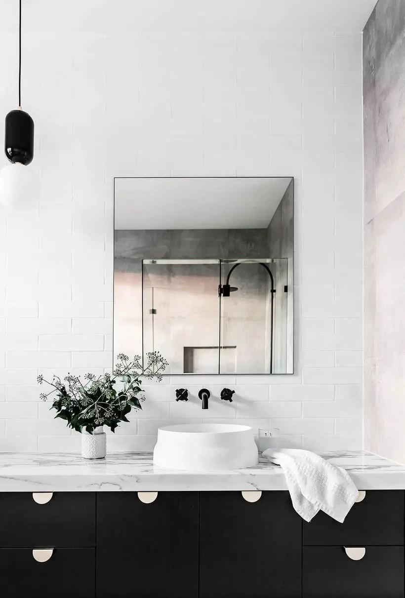A small bathroom monochrome color design with white brick walls, a square mirror on the walls, a white granite table, a house plant, and black storage cabinet bathroom