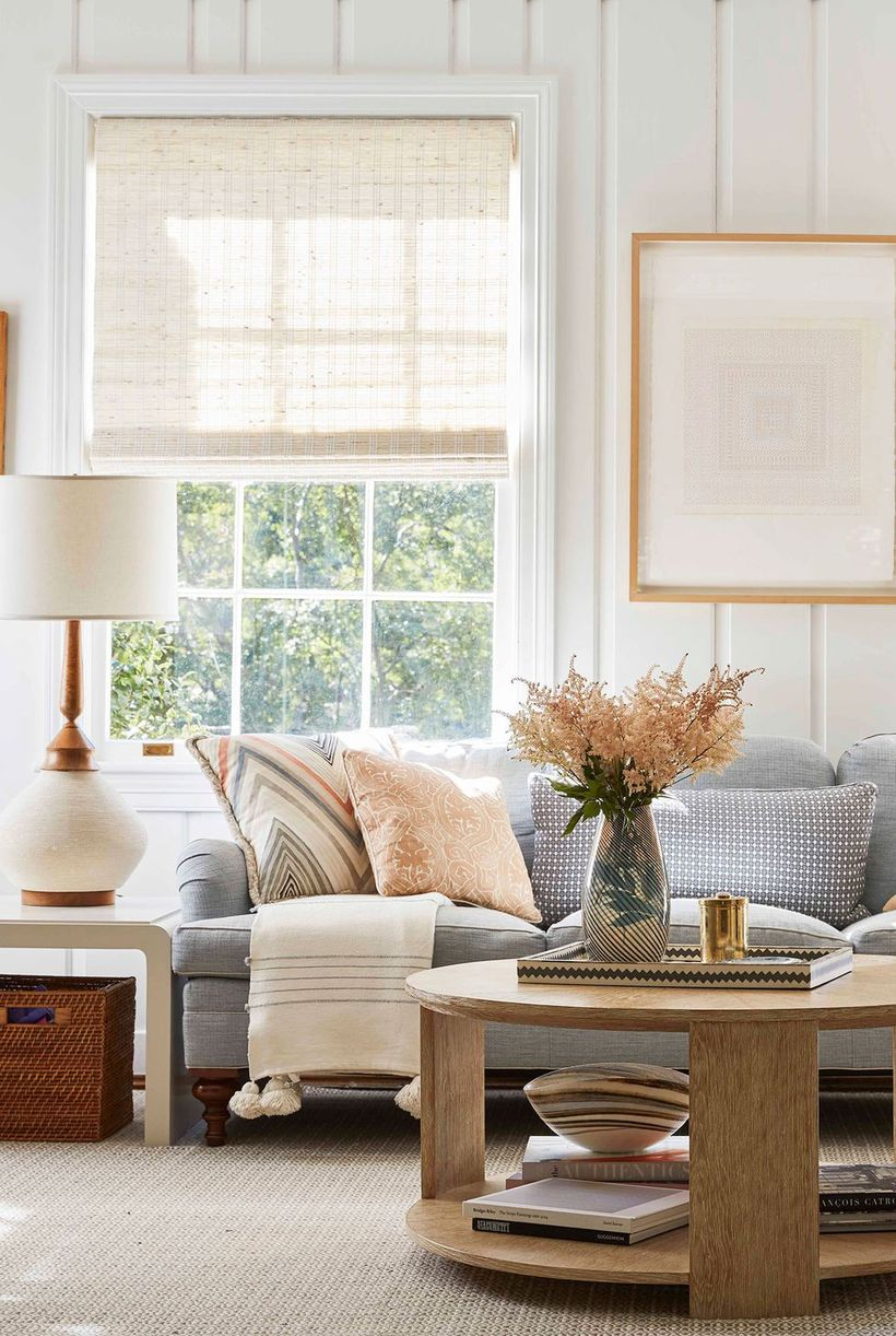 A small living room design with white walls, a large window, a grey sofa, a round coffee table, and a house plant to create a cozy