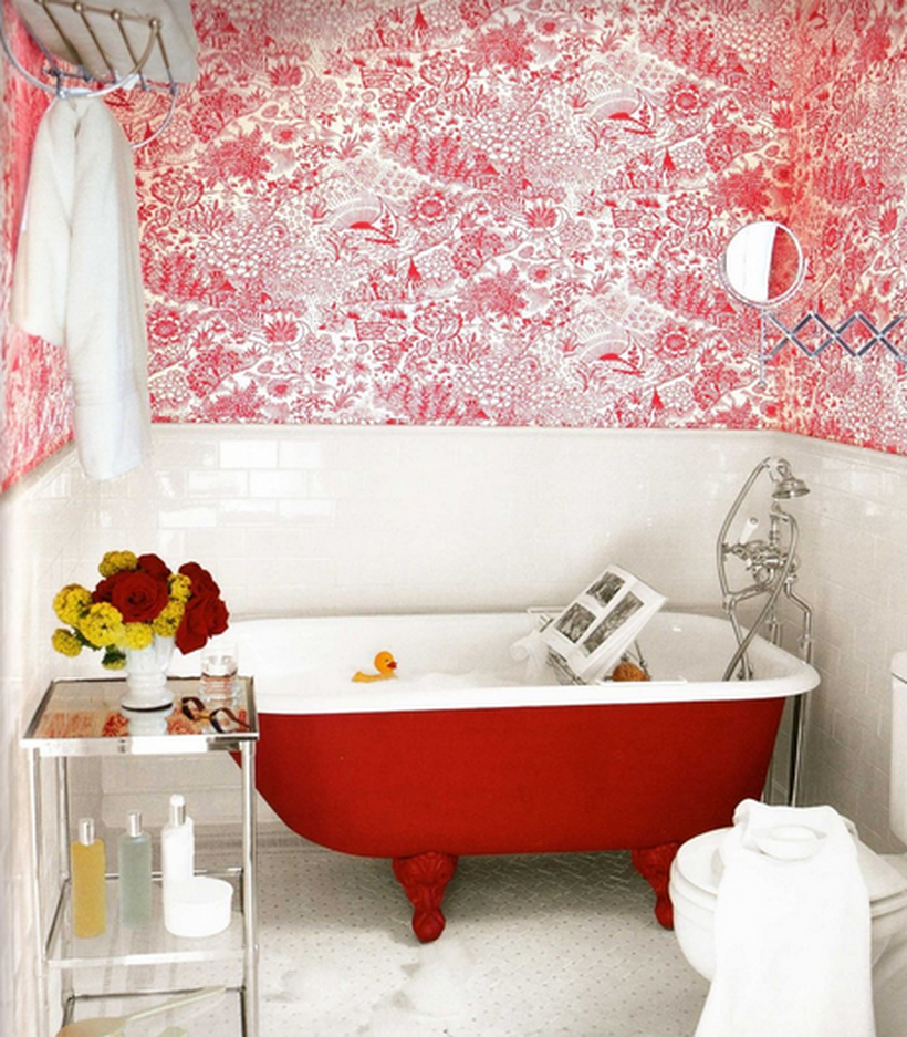 A unique small bathroom decor ideas with red wallpaper, and brick ceramic walls, a red and white bathtub, a towel hook, small metal table to put some toiletries and a house plant