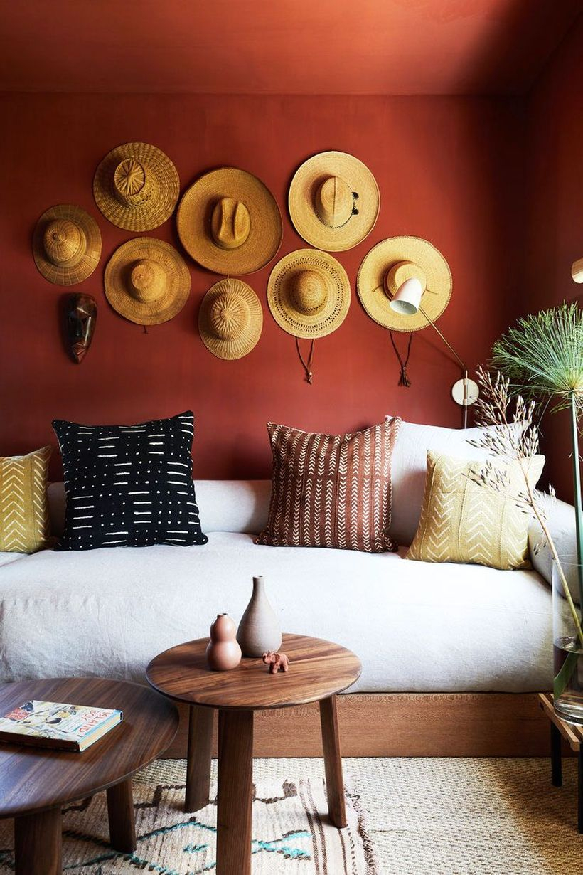 A white sofa in a small family with wooden round coffee tables and hat decoration on the walls