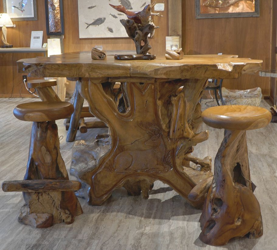 An attractive small teak wood furniture with round wooden table, wooden chairs, wooden floor and wooden walls
