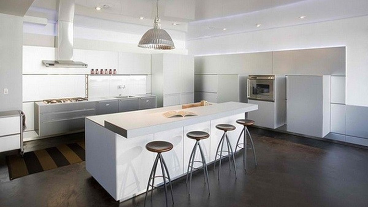 An impressive modern white kitchen design with white kitchen cabinet storages, a large white kitchen island, and decorative lighting to create good light