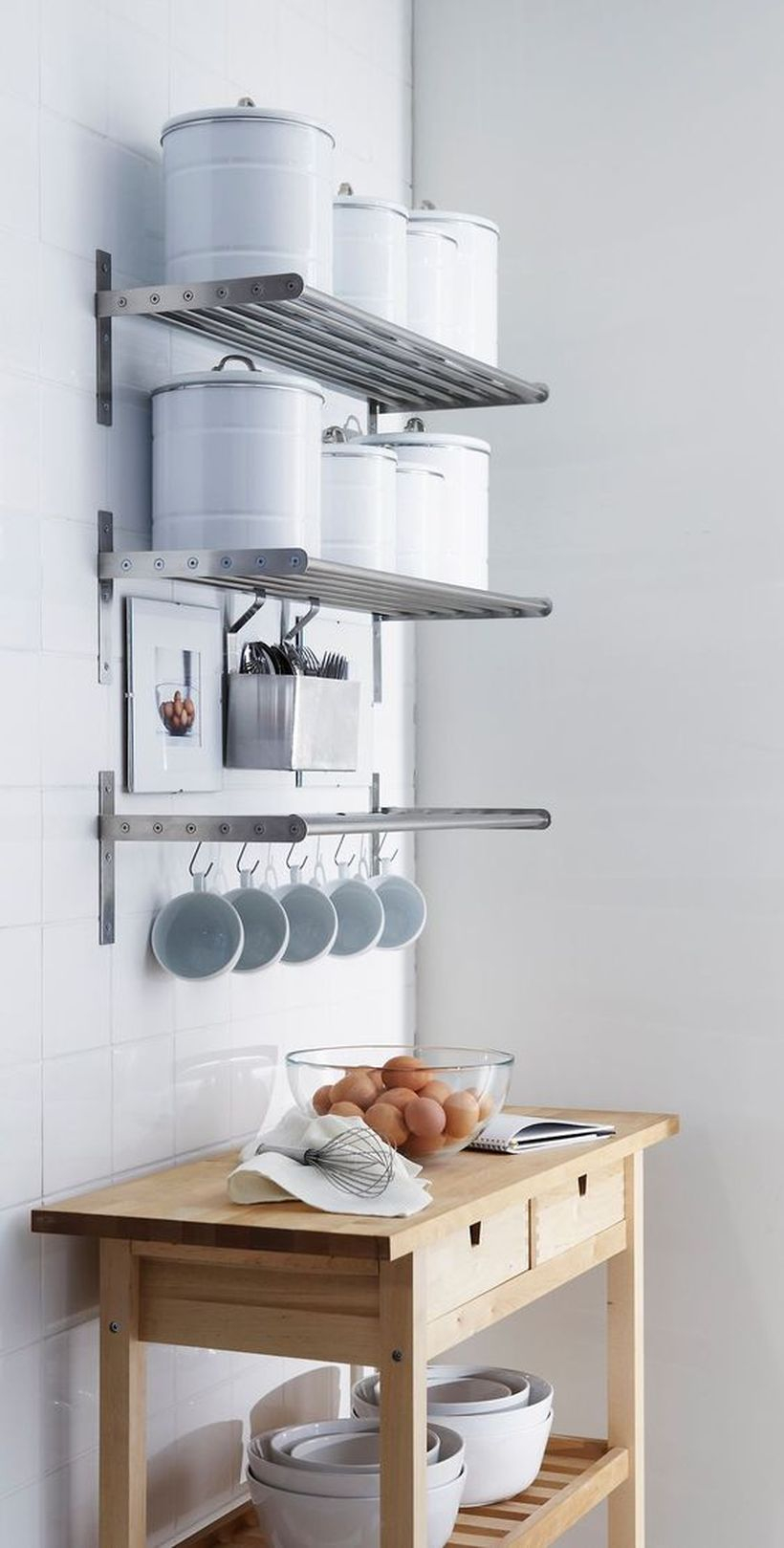 Hanging rack that made of metal to put some kitchen appliance and table with drawers and storage on below to store some bowls