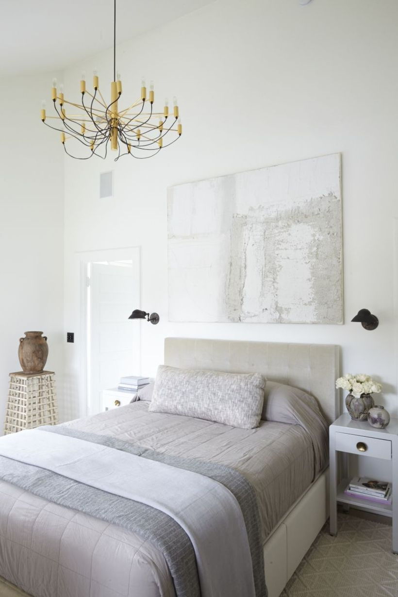 The minimalist bedroom with neutral palette, modern art on the walls, a vintage nightstands and a statement chandelier to create good lighting