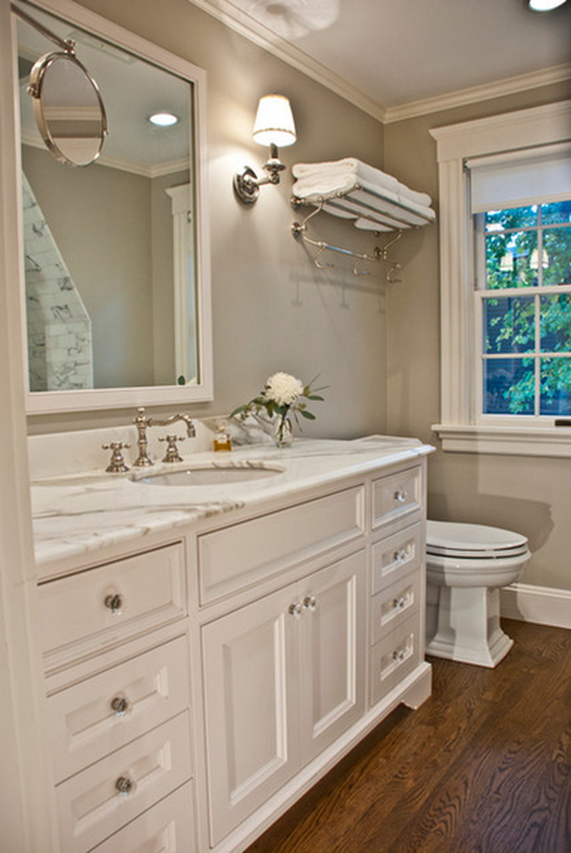 Traditional bathroom decor ideas with a towel hook on the walls, white storage cabinet, a big mirror, and decorative lighting