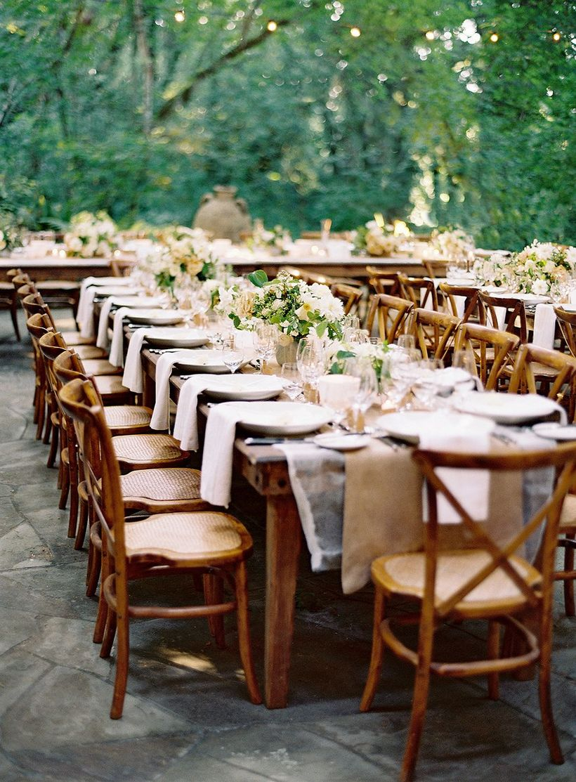 A fabulous outdoor table set for wedding with short wooden table, wooden chairs, white tablecloth and flower decoration on the table.