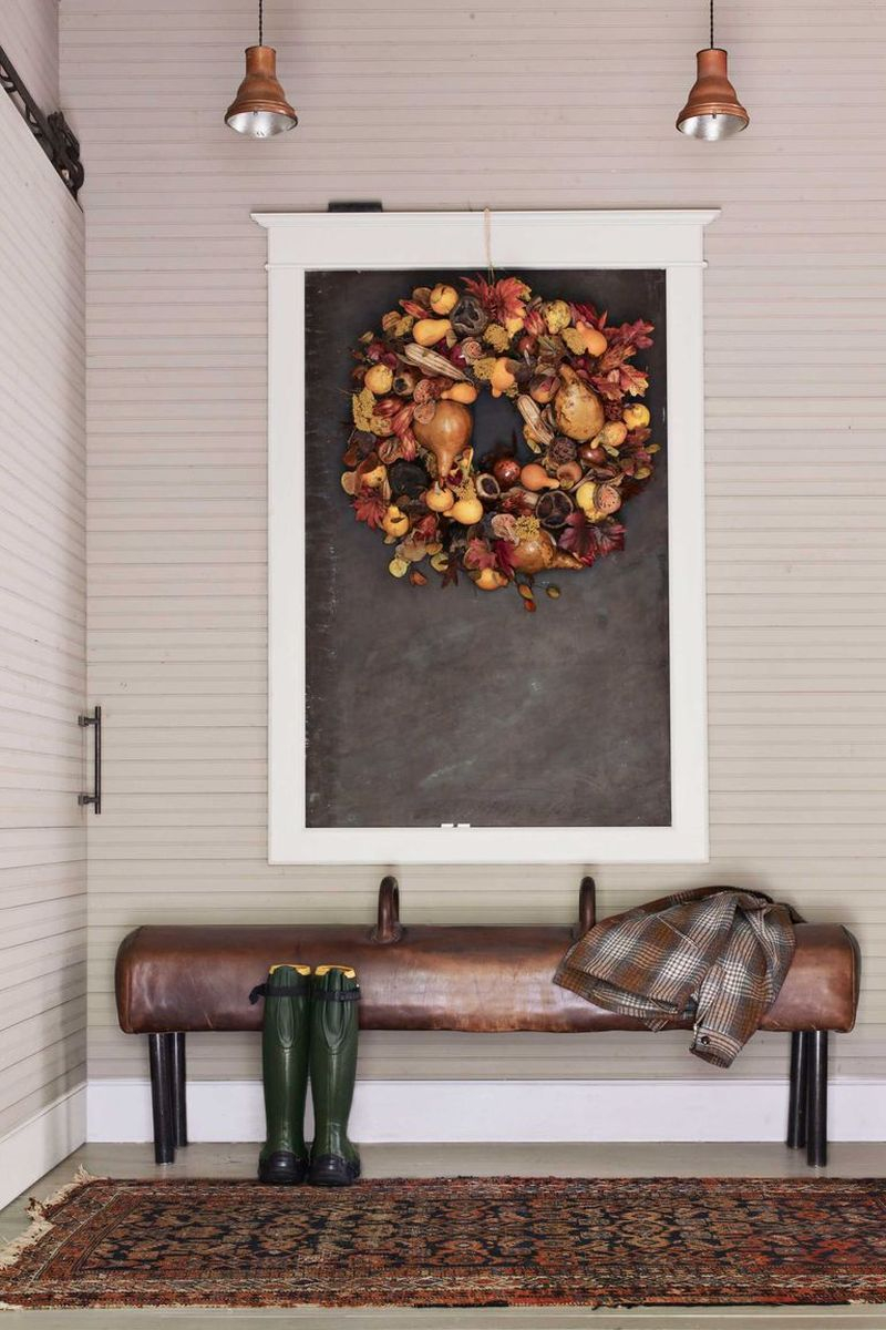A gymnastics pommel horse with its legs shortened, serves as a bench in a entryways and the seasonal wreath hangs on a framed chalkboard