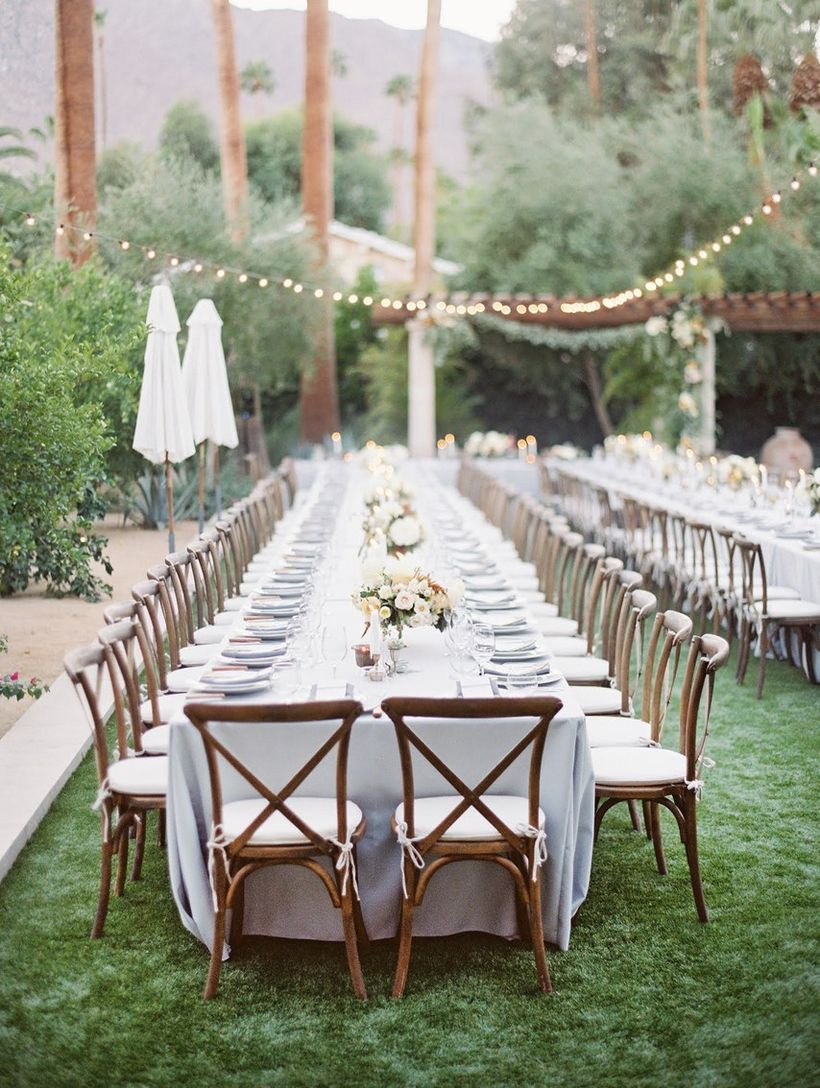 A magnificent outdoor table set for wedding with a long romantic table with floral centerpieces, crisp white dinnerware, green grass and rustic cross-back chairs.