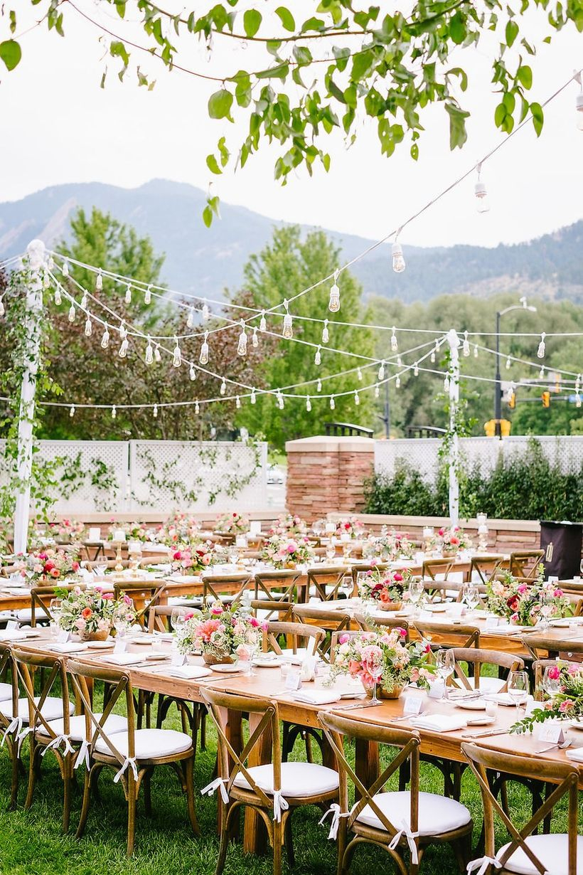 A stunning outdoor table set for wedding with long wooden tables, white tablecloths, wooden chairs, chandeliers and flower decoration on the table.