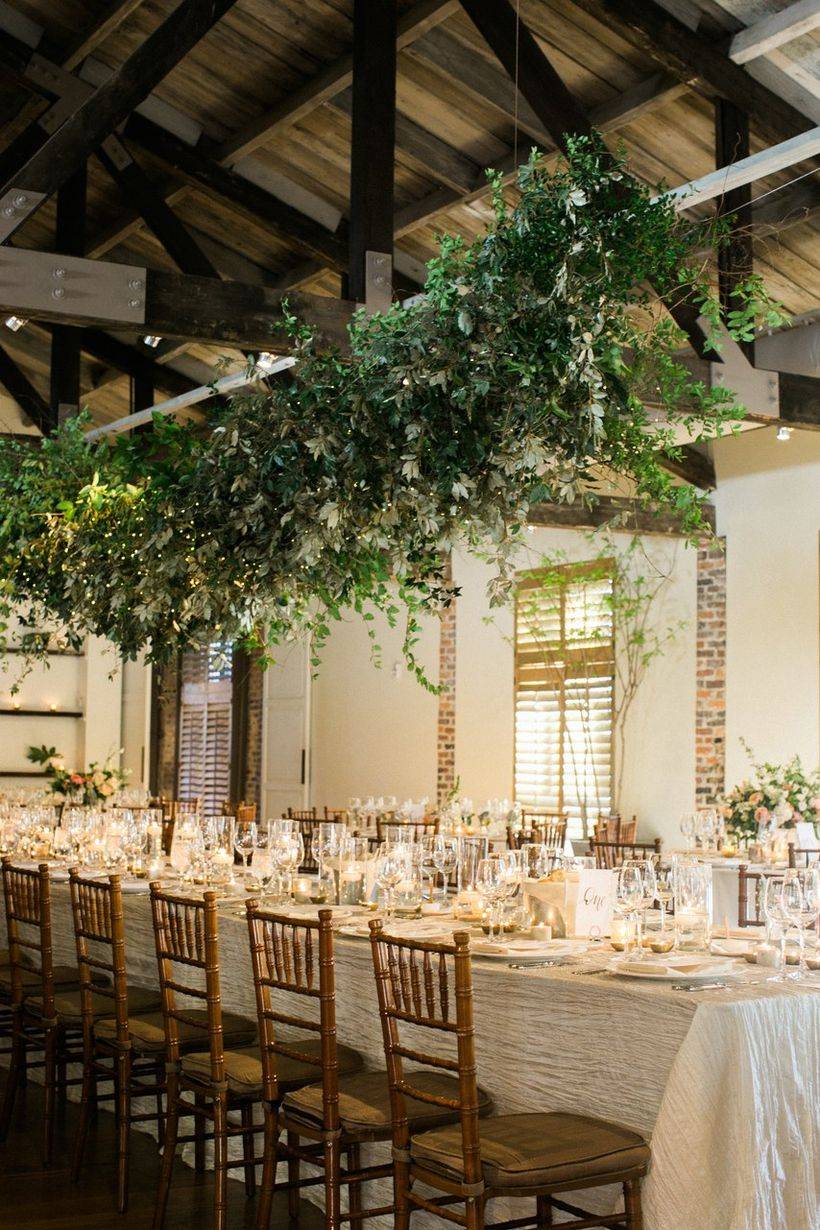 A wonderful indoor table set for wedding with long iron table, hanging greenery wedding greenery installation feels wild whimsical and a perfect.