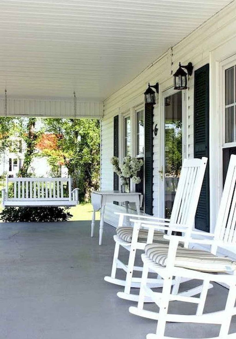 An awesome farmhouse porch furniture with white wooden chairs, a square white wooden table and a hanging white chair