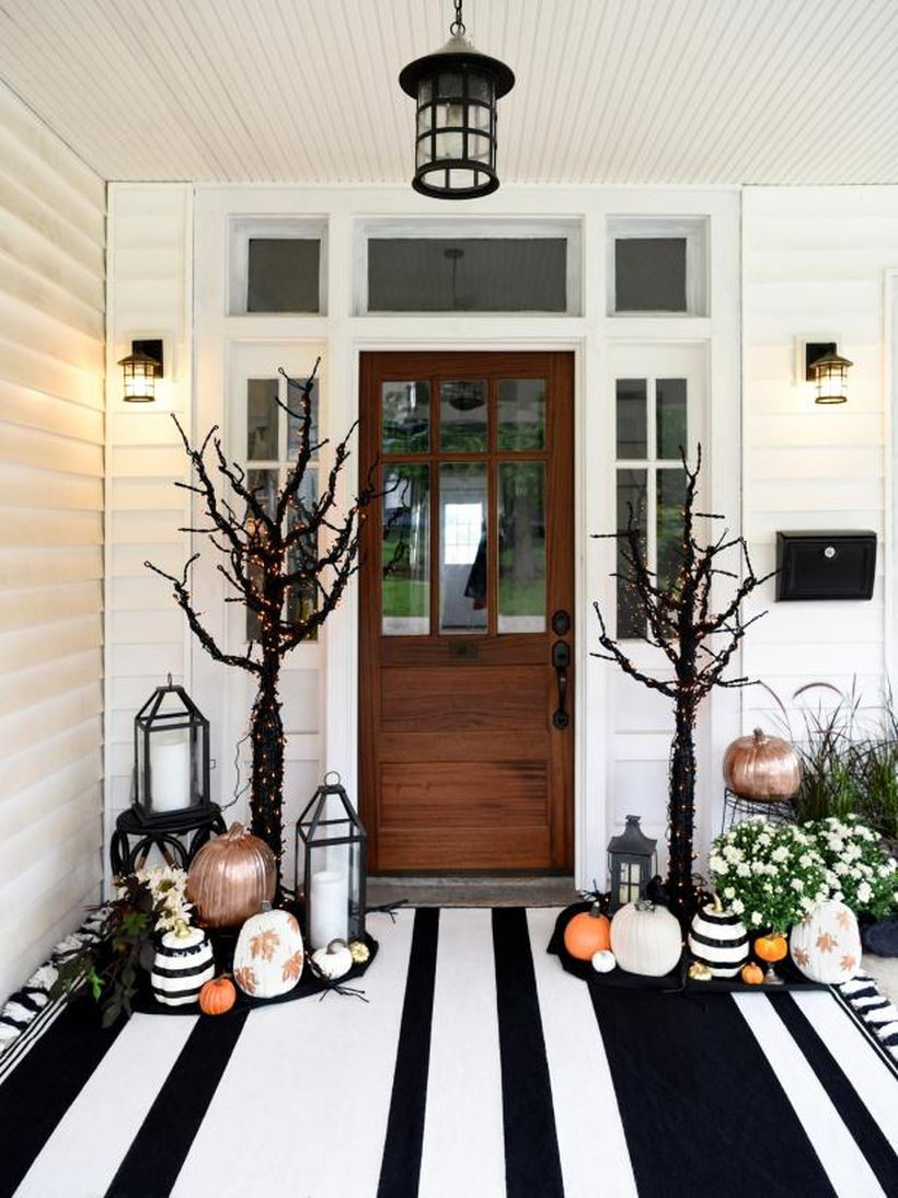 An awesome front porch fall with pumpkins, candle lights, white flower plants, a hanging lamp, lights on the walls, and dried tree lights