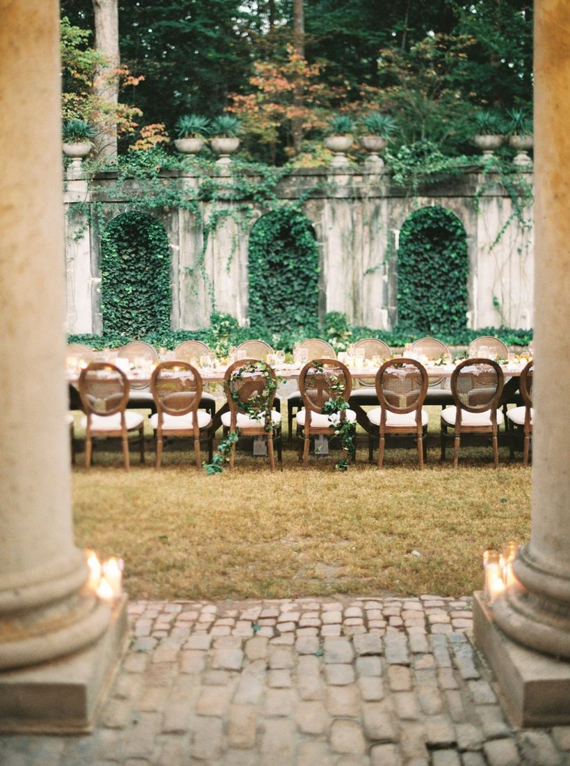 An amazing outdoor table set for wedding with a long wooden tables, wooden chairs, lush plants and crisp grass.