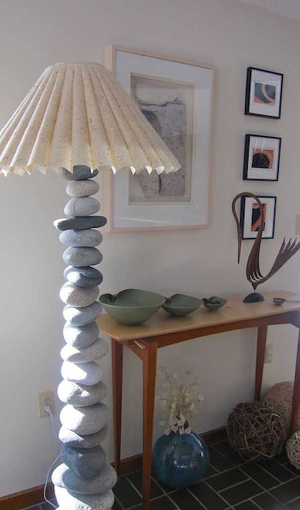 An awesome stone lamp combined with white walls, wooden table, wall gallery and dark floor to bringing natural elements into your home