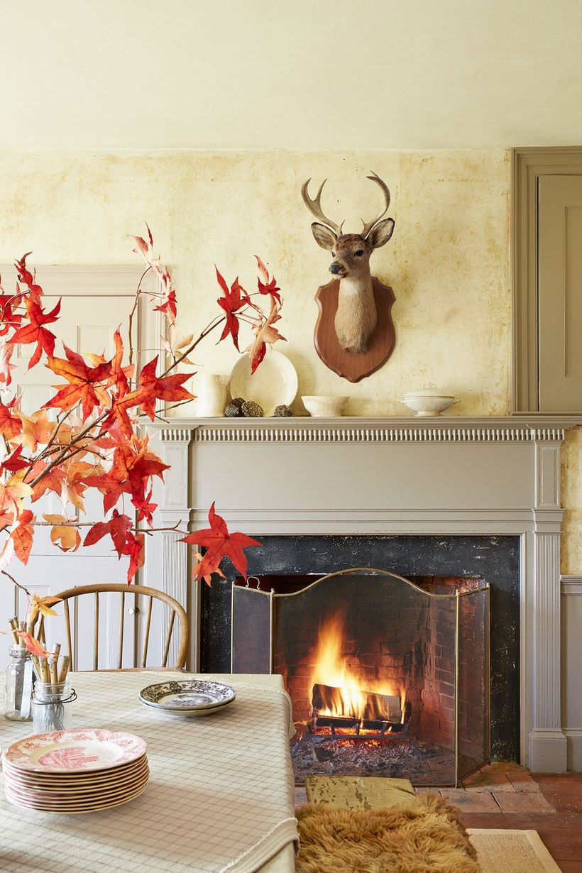 An extraordinary indoor redecoration from summer to fall with fireplace, wooden table, simple vase and wall decoration