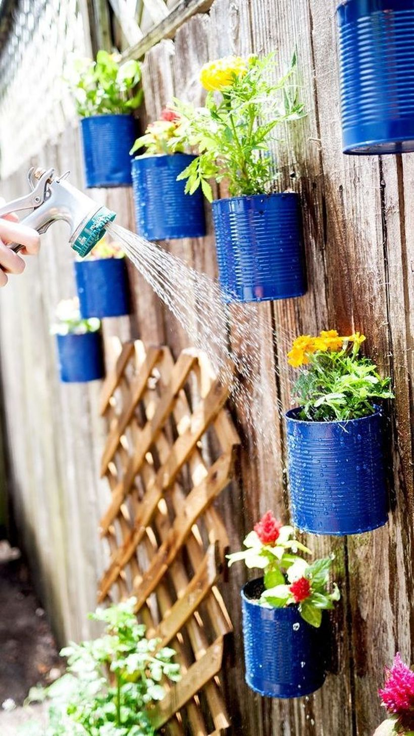 An impressive plant decoration for fence with upcycled tin can planters to decorate your fence with live flowers and it's a really easy project to complete.
