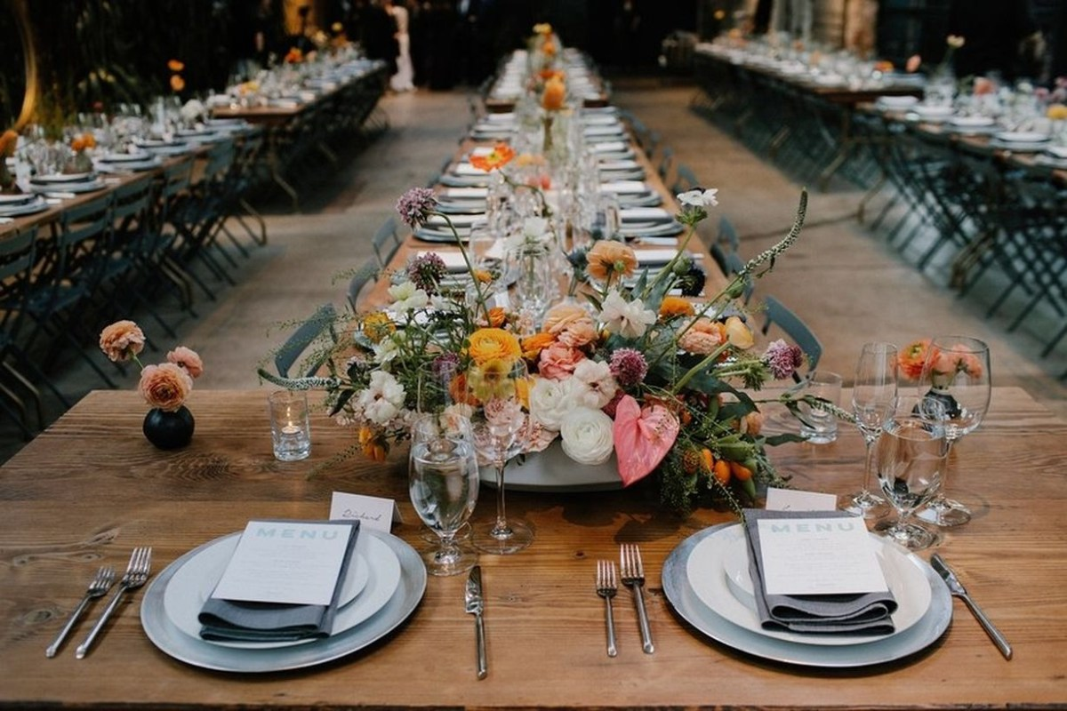An incredible indoor table set for wedding with long bare wooden tables mirror the industrial and are dressed up modern tropical centerpieces in bright poppy colors.