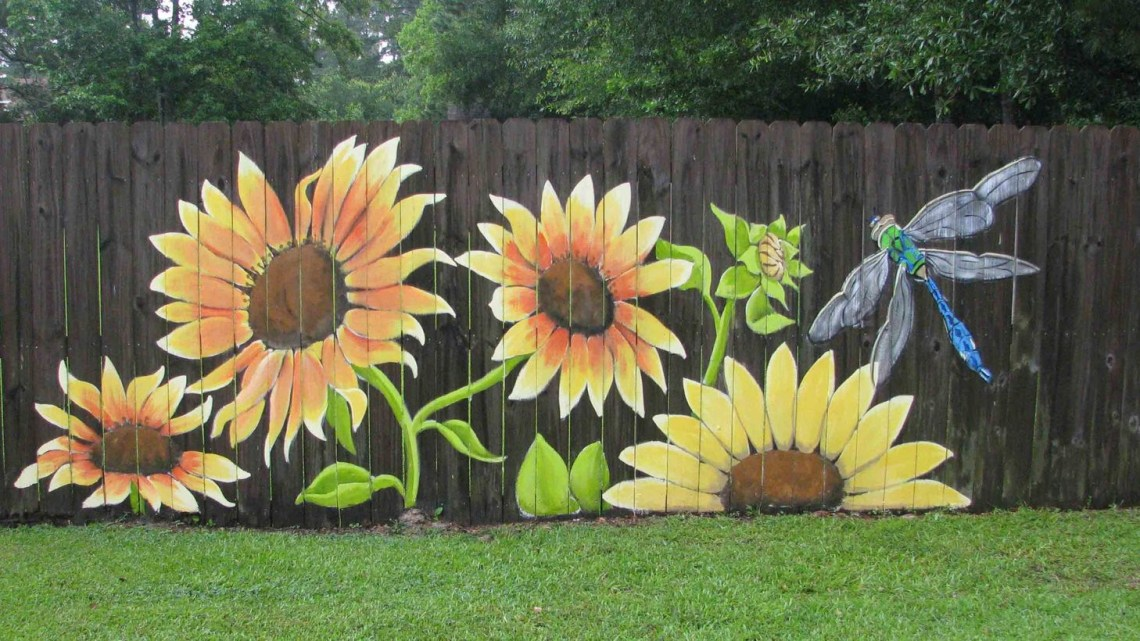 An incredible painting fence for garden with full sunflowers and dragonflies that get a look that's bright and cartoon inspired but still with a little bit of impressive detail for balance.
