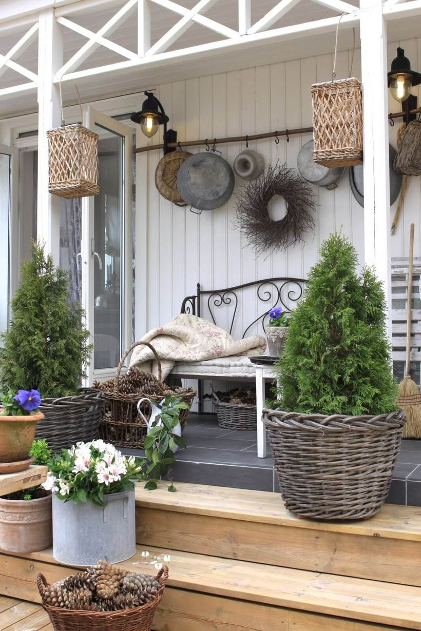 Beautiful farmhouse porch ornament with plants in rattan pots, hanging rattan ornaments, and black lights on the wall