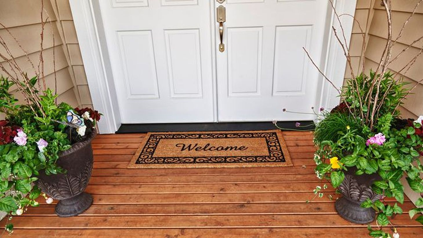 Charming farmhouse porch ornament with patterned black pot plants and a brown carpet to complete your front yard
