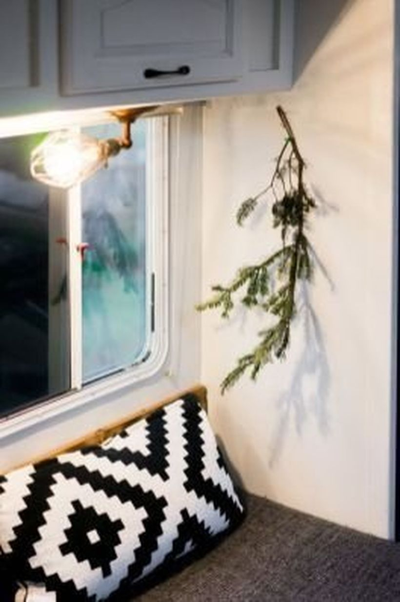 Simple rv decor with piece fresh pine leaves, pendant lamps and pillow motifs