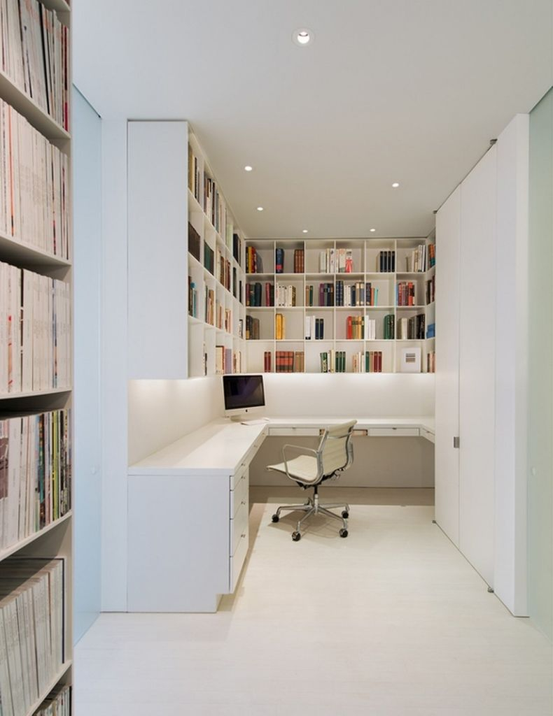 Stunning home office featuring white bookshelves and has white floors, white walls, a white desk with drawers to perfect your home office
