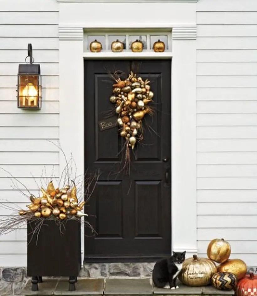 Cozy fall porch decorating ideas with gold pumpkin wreath, and gold pumpkin arrangement