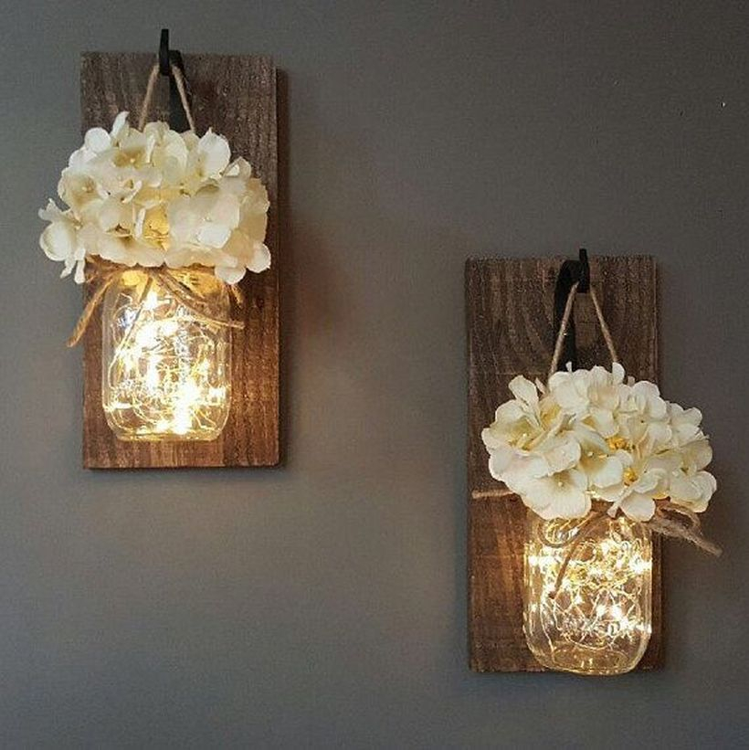 Rustic wall art ideas with glowing mason jar wall sconces to create a cozy room