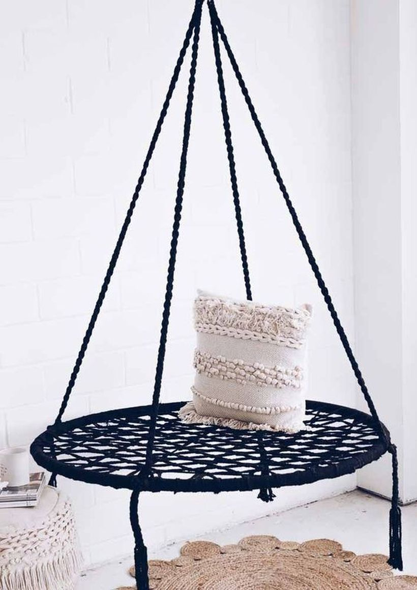 A black macrame boho seat with a boho pompom pillow.