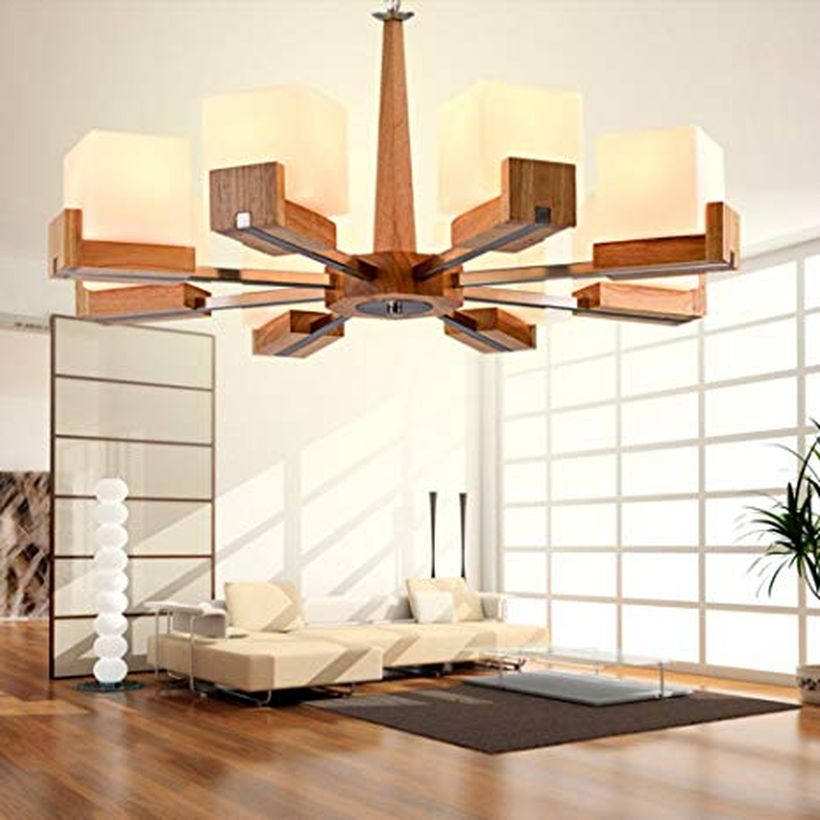 A comfortable rustic chandelier for living room with nostalgic chandelier, wooden vinyl floor, letter l white sofa, house plant and a black carpet.