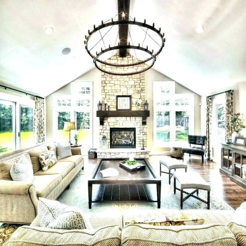 A fabulous rustic chandelier for living room with large round chandelier, patterned sofas, black wooden table, large carpet, a fireplace and large glass wall.