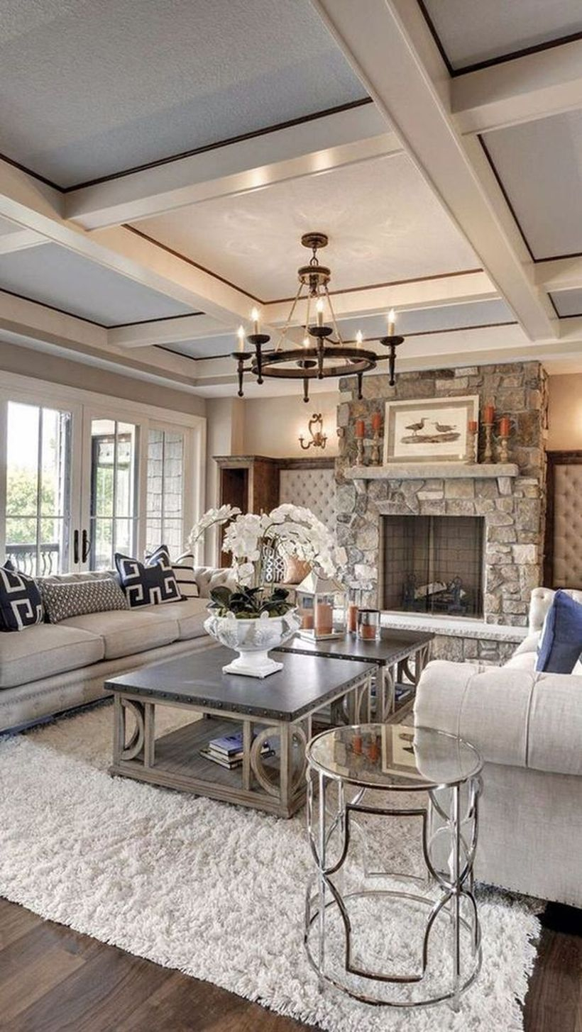 A stunning rustic chandelier for living room with round wooden rustic chandelier, grey sofa, black tables, white rug, big windows and decoration on the table.