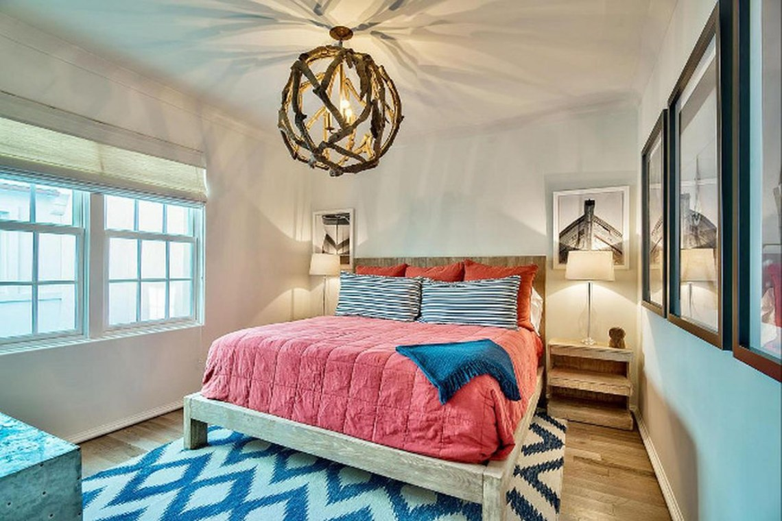 A unique rustic chandelier for bedroom with florida chandelier, pink bed linen, patterned carpet, small table, wooden floor and windows large.