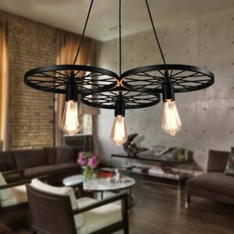 An adorable rustic chandelier for living room with 3 black wagon wheel chandelier, brown sofas, white chairs, wooden floor, brick stone wall and round white table.
