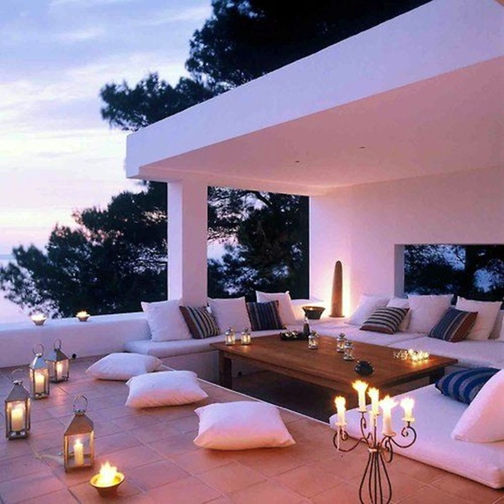 An amazing small rooftop lighting with candle lights combined white sofa and wooden table to perfect your rooftop design